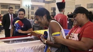 An admirer weeps as she look on Chavez in his coffin. Photo credit: AFP