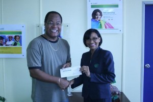 Main organizer of the Teen pageant receives donation from a representative of the bank