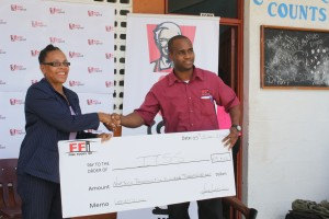 ITSS principal Shirley Samuel receives cheque from FFI Marketing Officer Lennan Matthew