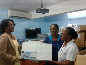 Joycelyn Graham Laronde (left) presents the supplies to a nurse at the Roseau Health Center