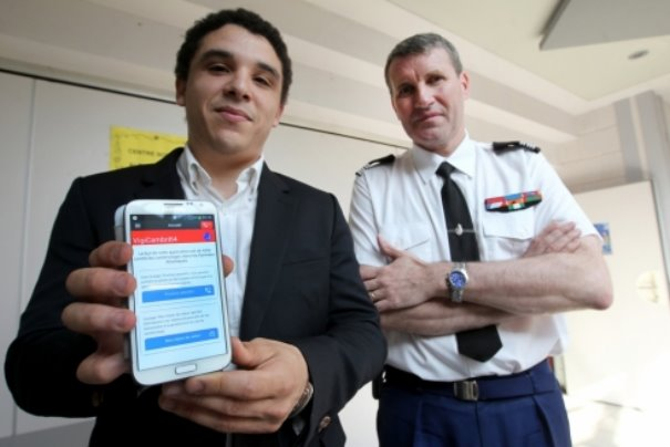 Elie Poussou shows off the app while a law enforcement officer looks on