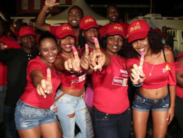 PNM supporters show off their stained fingers during victory celebrations at Balisier House, Port-of-Spain, last night. Photo: JEFF MAYERS