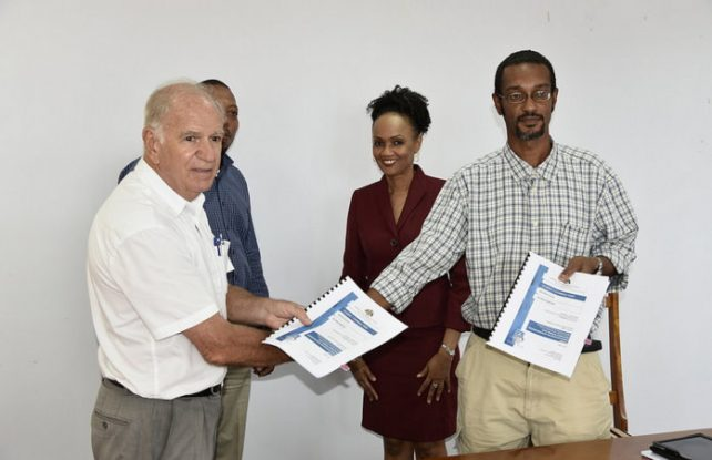 Anthony Burnette-Biscombe of La Robe Creole Limited (left) exchanges contract with Permanent Secretary in the Ministry of Public Works, Kendall Johnson. In the background is Public Works Minister Miriam Blanchard and Emile Lancelot