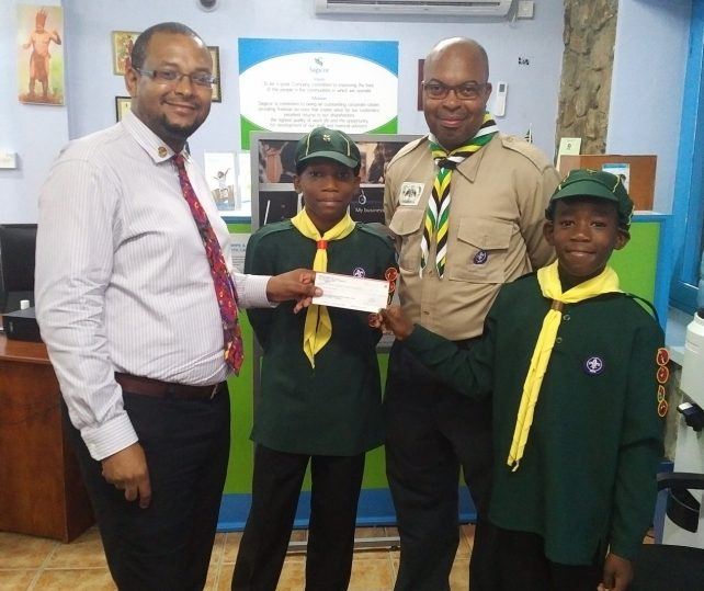 Brenton Hilaire, Agency Manager of Sagicor Life Inc presenting the company's donation to cub scouts before their trip to the Cuboree